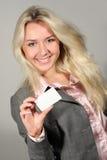 Señora sonriente que sostiene la tarjeta en blanco Imagen de archivo