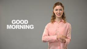 Señora sorda que dice buena mañana en el lenguaje de signos, texto en la comunicación del fondo almacen de metraje de vídeo