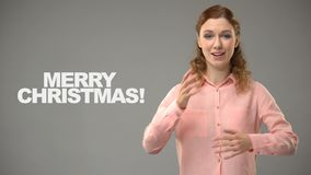 Señora sorda que dice Feliz Navidad en el lenguaje de signos, texto en el fondo, sordera almacen de metraje de vídeo