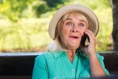 Señora sorprendida con un teléfono Imagenes de archivo