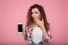 Señora sorprendida que muestra smartphone con la pantalla en blanco aislada Imagenes de archivo