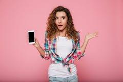Señora sorprendida que muestra smartphone con la pantalla en blanco aislada Fotos de archivo