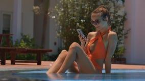 Señora Speaks en la sentada móvil en piscina