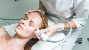 Señora tranquila que tiene procedimiento facial del rejuvenecimiento de la piel almacen de metraje de vídeo