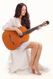 Señora triguena joven que toca la guitarra acústica fotos de archivo