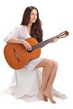 Señora triguena joven que toca la guitarra acústica fotografía de archivo libre de regalías