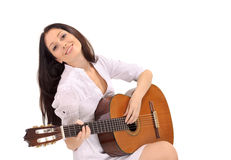 Señora triguena sonriente joven que toca la guitarra imagen de archivo libre de regalías
