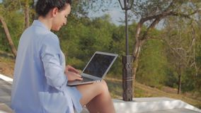 Señora Working en el ordenador portátil, morenita atractiva en un traje azul con un ordenador portátil, mujer atractiva del negoc almacen de video
