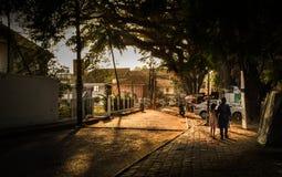Señora y niño que caminan en una calle en la mañana foto de archivo