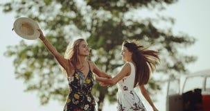Señoras bastante jovenes con el baile largo del pelo feliz en el medio de la naturaleza que lleva un vestido retro elegante metrajes