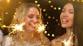Señoras bonitas que llevan a cabo las luces de Bengala en la fiesta de Navidad, riendo y divirtiéndose metrajes