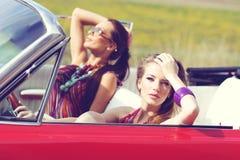 Señoras hermosas con los vidrios de sol que montan un coche retro del vintage Fotos de archivo libres de regalías