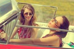 Señoras hermosas con los vidrios de sol que presentan en un coche del vintage en un verano de la primavera del día soleado Fotos de archivo
