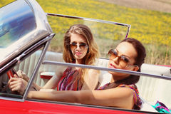 Señoras hermosas con los vidrios de sol que presentan en un coche del vintage en un verano de la primavera del día soleado Imagenes de archivo