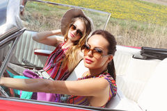 Señoras hermosas con los vidrios de sol que presentan en un coche del vintage en un verano de la primavera del día soleado Fotos de archivo libres de regalías