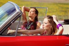 Señoras hermosas con los vidrios de sol que presentan en un coche del vintage en un verano de la primavera del día soleado Imagen de archivo
