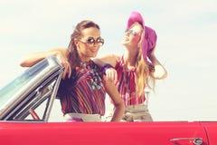Señoras hermosas con los vidrios de sol que presentan en un coche retro del vintage Imagen de archivo
