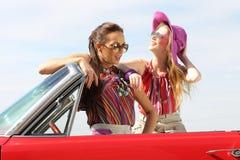 Señoras hermosas con los vidrios de sol que presentan en un coche retro del vintage Fotografía de archivo