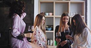 Señoras hermosas del buen humor que disfrutan del tiempo junto mientras que celebra el partido de la soltera en casa en un estudi almacen de video