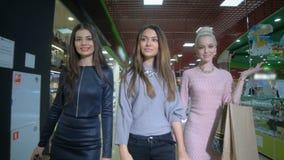 Señoras hermosas que caminan en una tienda con los panieres Cámara lenta