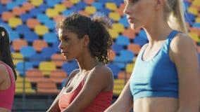 Señoras hermosas que hacen los ejercicios físicos en el estadio, alcohol de la competencia almacen de video