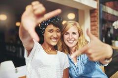 Señoras jovenes de la diversión que enmarcan sus caras Imagen de archivo libre de regalías