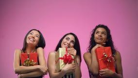 señoras jovenes Multi-étnicas que llevan a cabo presentes y que miran para arriba la plantilla, celebraciones metrajes