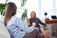 Señoras magníficas que ríen mientras que bebe el café en sala de estar Foto de archivo