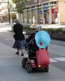 Señoras mayores que caminan y que montan una vespa de la movilidad en el centro de la ciudad de Vancouver imágenes de archivo libres de regalías