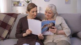 Señoras mayores que leen la revista moderna con el placer, mucho información interesante almacen de metraje de vídeo