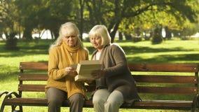 Señoras mayores que miran la foto del amigo difunto en banco en el parque, años de oro almacen de metraje de vídeo