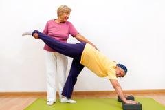 Señoras mayores que se ayudan con estirar ejercicio Imagen de archivo