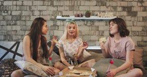 Señoras muy bonitas que comen la pizza en casa en dormitorio y tener una conversación divertida con uno a, en el gasto de los pij metrajes