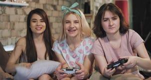 Señoras muy impresionantes que disfrutan del tiempo junto delante de la cámara que juega en un juego de Playstation en la noche d almacen de video