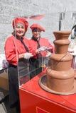 Señoras que preparan los pinchos de la fruta con una fuente del chocolate Fotos de archivo libres de regalías