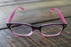 Señoras rosadas elegantes que leen las lentes Imagen de archivo libre de regalías