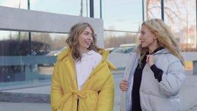 Señoras sonrientes encantadoras jovenes en capas en la calle metrajes