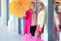 Señoras sonrientes que sostienen los paraguas coloridos Fotografía de archivo