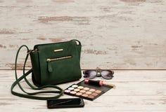 Señoras verdes bolso, gafas de sol, teléfono, sombra de ojos y lápiz labial en fondo de madera Concepto de la moda con el espacio Fotografía de archivo libre de regalías