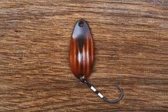 Señuelo pesquero hecho a mano en la tabla de madera vieja imagen de archivo libre de regalías
