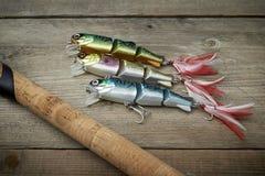 Señuelos coloridos con la caña de pescar en el embarcadero de madera fotos de archivo