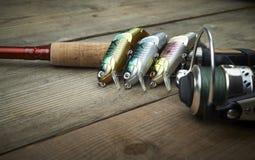 Señuelos coloridos con la caña de pescar en el embarcadero de madera foto de archivo