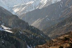 Se över dalöverskriften in mot sjön Tilicho och de branta sidbergen av himalayasna På den Annapurna strömkretsen n arkivbild
