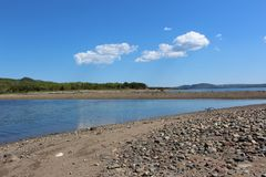 Se över raksträckan till fastlandet på en stenig strand på uddeBretonön arkivbild
