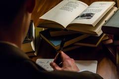 Se över skuldran av en man som skrivar ett brev, medan läsa litterära arbeten Arkivbild