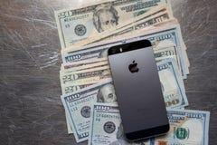 SE Яблока Iphone на куче валюты Соединенных Штатов стоковое фото rf