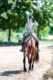 Se acaba el entrenamiento Muchacha que monta un caballo en la escuela ecuestre Foto de archivo