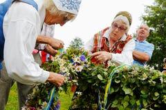 Se adhiere la guirnalda de flores en el Maypole foto de archivo