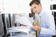 se affärsmannen för skrivbordsarbetemateriel though royaltyfria bilder