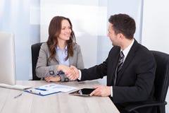 Se affärsmannen, medan skaka handen på kontorsskrivbordet Royaltyfri Foto